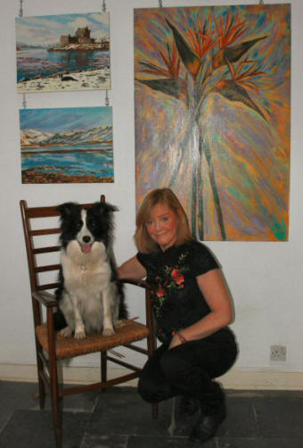 Caroline McCormack and Poppy posing in front of a selection of Caroline's oil paintings.